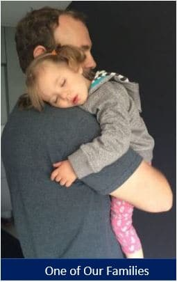 Father hugging his adopted daughter after he qualified to adopt.