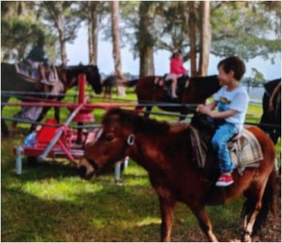 Adopted child riding a horse for fun.