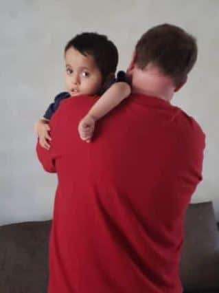 Dad holds his adopted son in Bulgaria.